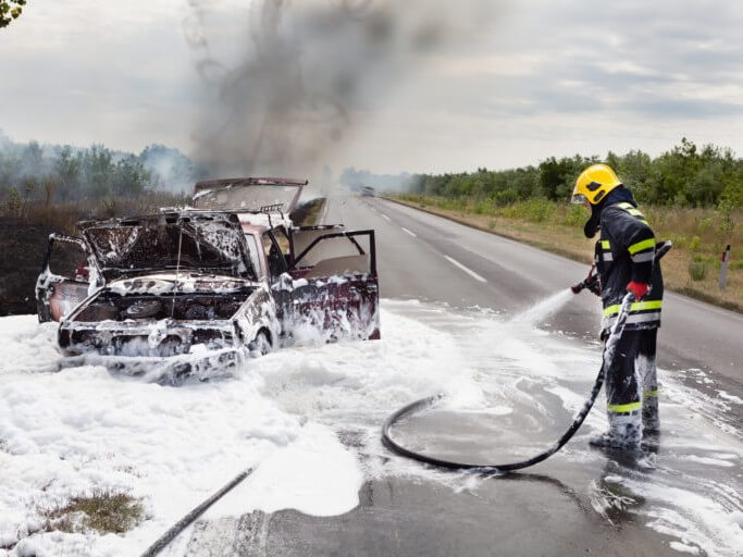 Photo of firefighter using foam to put out a car fire