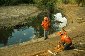 Workers lay geo-textiles to stabilize river banks in the Foster flood-plain.