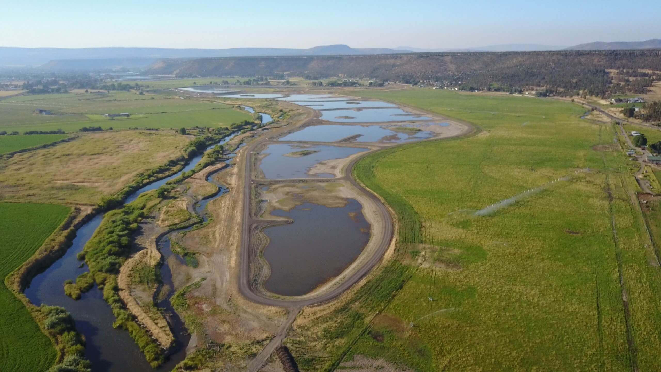 Prineville wetlands project - built ponds of water spread out on the landscape next to the natural path of a river.