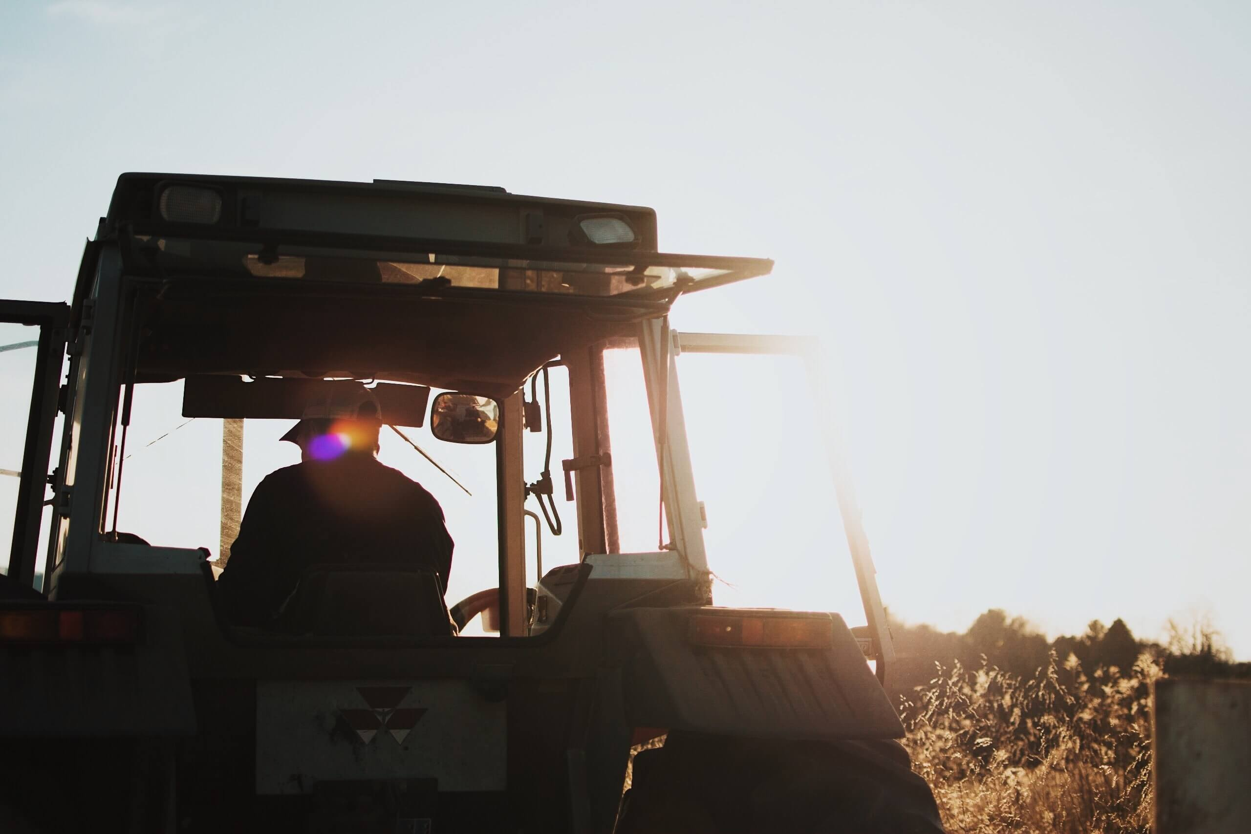 silhouette of person in tractor working a field