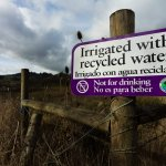 """Sign on fence post reading, """"Irrigated with recycled water""""."""